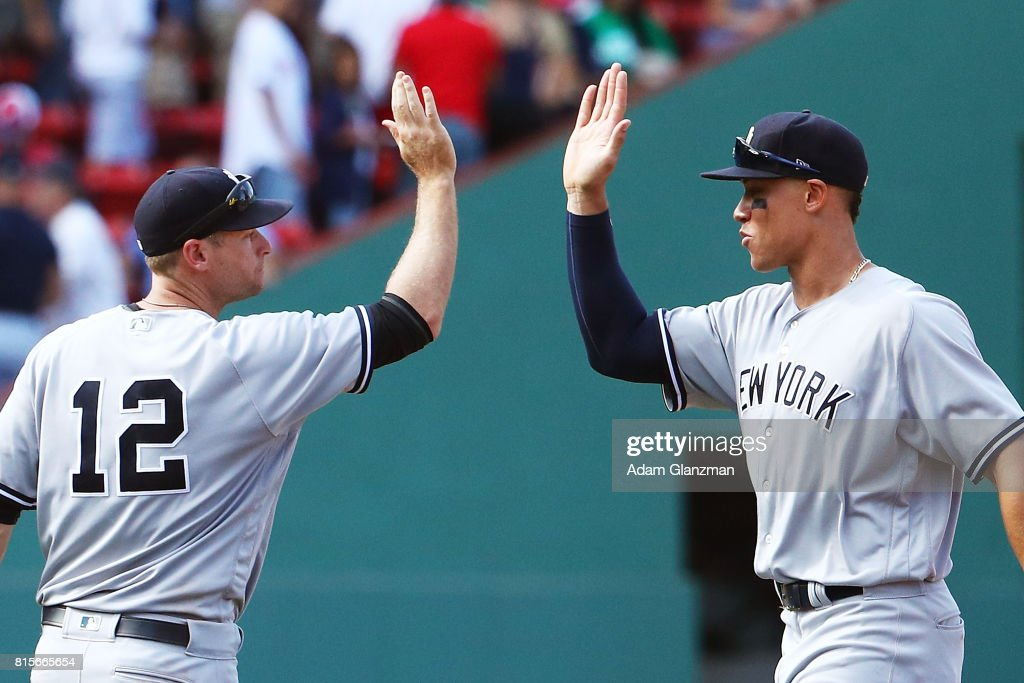 Chase Headley #12 high fives Aaron Judge #99 of the New York Yankees after the victory in game one of a doubleheader against the Boston Red Sox at Fenway Park on July 16, 2017 in Boston, Massachusetts.