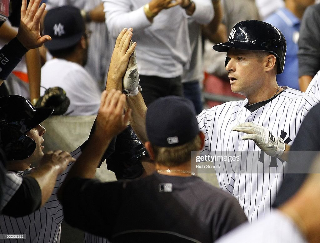 Chase Headley #12 of the New York Yankees is congratulated after he hits a home run during the fifth inning against the Detroit Tigers in a MLB baseball game at Yankee Stadium on August 6, 2014 in the Bronx borough of New York City.