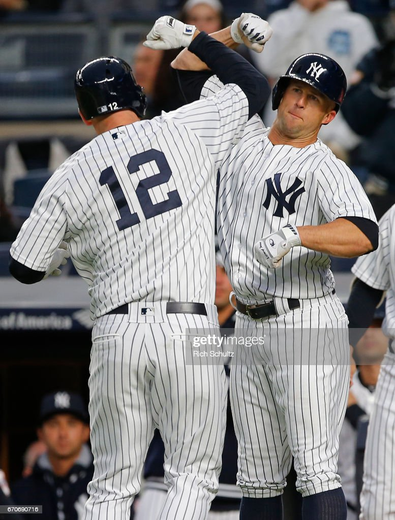 Chase Headley #12 of the New York Yankees is congratulated by Brett Gardner #11 after both scored on Headley's two-run home run against the Chicago White Sox during the first inning of a game at Yankee Stadium on April 19, 2017 in the Bronx borough of New York City.