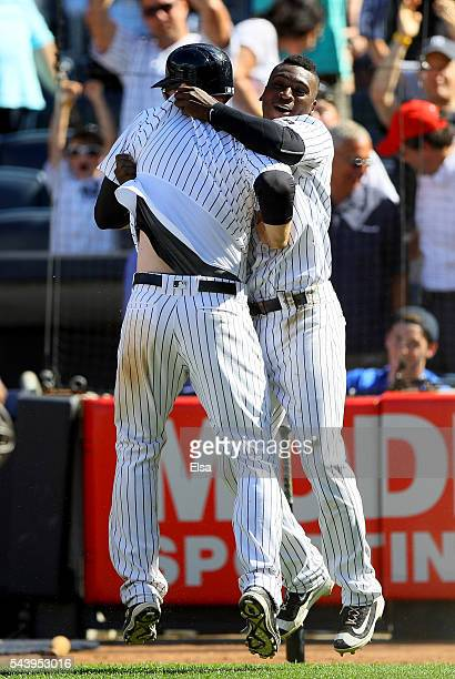 Chase Headley of the New York Yankees is congratulated by teammate Didi Gregorius after Headley scores on a passed ball in the ninth inning against...