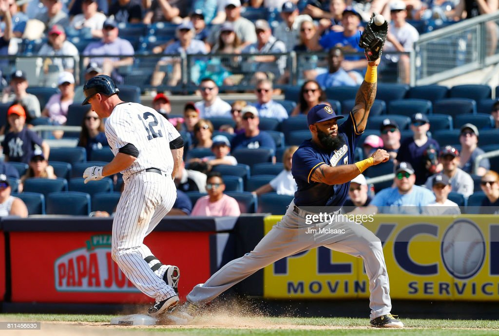 Chase Headley #12 of the New York Yankees reaches first base as Eric Thames #7 of the Milwaukee Brewers can't come up with the throw during the eighth inning at Yankee Stadium on July 9, 2017 in the Bronx borough of New York City.
