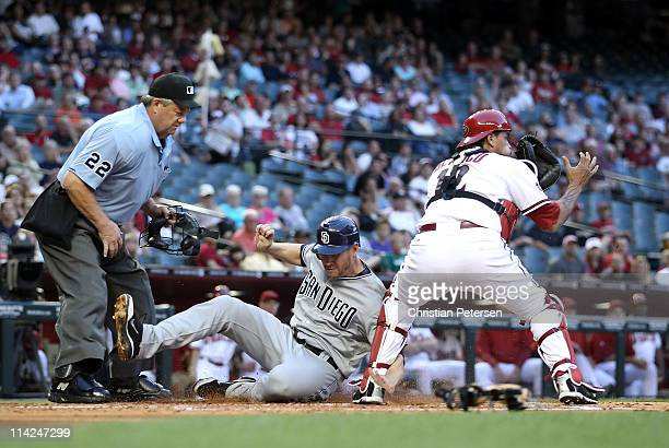 Chase Headley of the San Diego Padres slides in to score a first inning run past catcher Henry Blanco of the Arizona Diamondbacks during the Major...