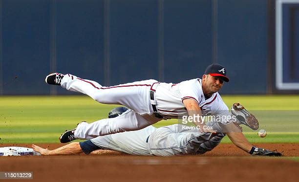Chase Headley of the San Diego Padres steals second base under Dan Uggla of the Atlanta Braves in the first inning at Turner Field on June 1 2011 in...