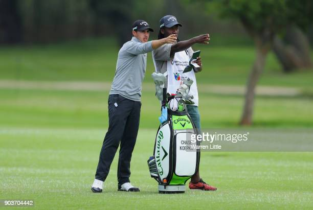 Chase Koepka of the United States and his caddie assess his second shot on the 18th hole during Day One of The BMW South African Open Championship at...