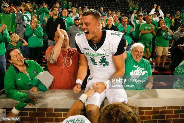 Chase Litton of the Marshall Thundering Herd celebrates with fans after defeating the Cincinnati Bearcats at Nippert Stadium on September 30 2017 in...