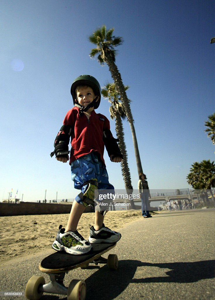 Chase Mann Green, 4, of Telluride, CO, rides his skateboard along the boardwalk at the Huntington Be : News Photo