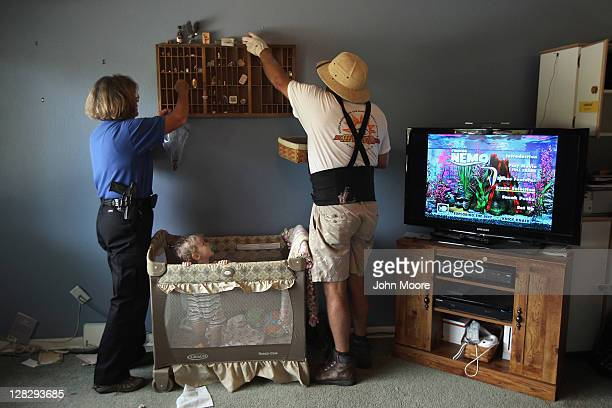 Chase Milam watches as an eviction team and sheriff's seputy remove household goods during a home foreclosure eviction on October 5, 2011 in...
