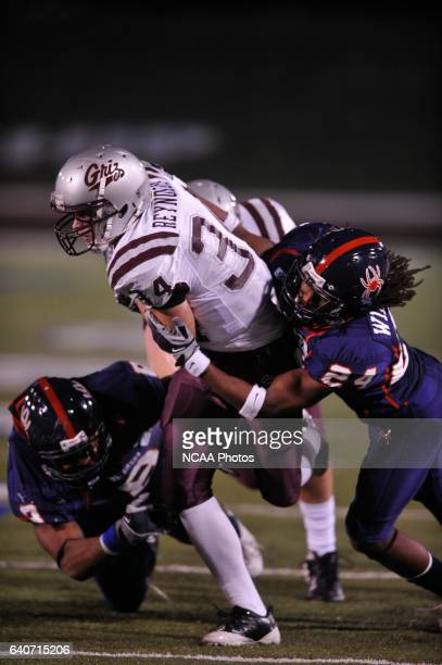 Chase Reynolds of Montana is tackled by Seth Williams and Sherman Logan of Richmond during the 2008 Division I Men's Football Championship held at...