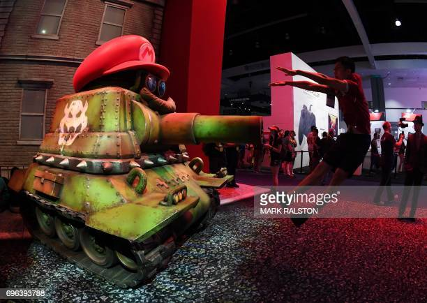 Chase Shi jumps beside a Nintendo Super Mario figure at the Los Angeles Convention center on day three of E3 2017 the three day Electronic...