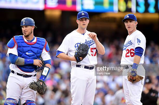 Chase Utley Alex Wood and Yasmani Grandal of the Los Angeles Dodgers wait for a ruling as Stephen Piscotty of the St Louis Cardinals takes first base...