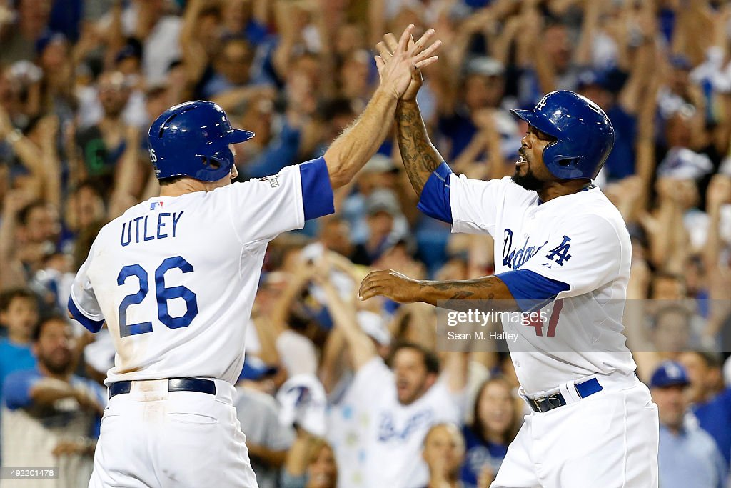 Chase Utley #26 and Howie Kendrick #47 of the Los Angeles Dodgers celebrate after scoring on a two-RBI double by Adrian Gonzalez #23 in the seventh inning against the New York Mets in game two of the National League Division Series at Dodger Stadium on October 10, 2015 in Los Angeles, California.