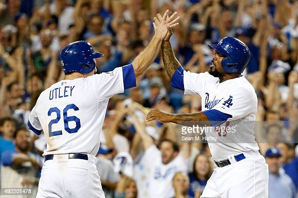 Chase Utley and Howie Kendrick of the Los Angeles Dodgers celebrate after scoring on a twoRBI double by Adrian Gonzalez in the seventh inning against...