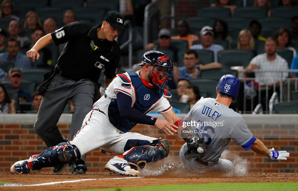 Chase Utley #26 of the Los Angeles Dodgers is tagged out as he attempts to score against Tyler Flowers #25 of the Atlanta Braves in the eighth inning at SunTrust Park on August 1, 2017 in Atlanta, Georgia.