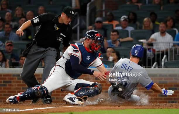 Chase Utley of the Los Angeles Dodgers is tagged out as he attempts to score against Tyler Flowers of the Atlanta Braves in the eighth inning at...