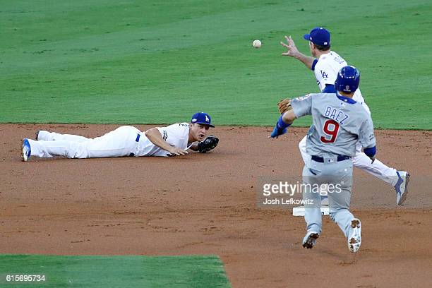 Chase Utley of the Los Angeles Dodgers is unable to bare hand a ball thrown to him by Corey Seager in the second inning as Javier Baez of the Chicago...