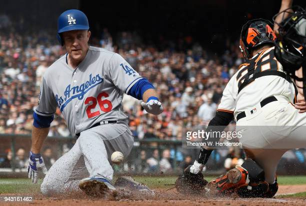 Chase Utley of the Los Angeles Dodgers scores ahead of the throw to Buster Posey of the San Francisco Giants in the top of the third inning of a...