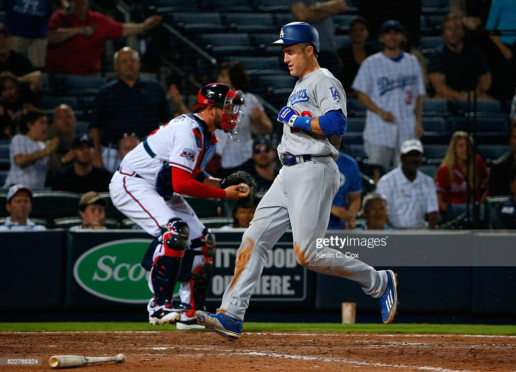 Chase Utley #26 of the Los Angeles Dodgers scores the go-ahead run on a RBI double hit by Justin Turner #10 in the 10th inning against the Atlanta Braves at Turner Field on April 20, 2016 in Atlanta, Georgia.