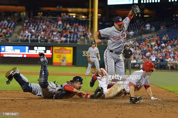 Chase Utley of the Philadelphia Phillies gets tagged out at home plate in the eighth by Jhonatan Solano of the Washington Nationals, as pitcher Craig...