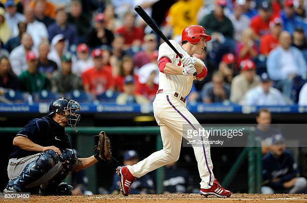 Chase Utley of the Philadelphia Phillies hits a tworun double in front of Jason Kendall of the Milwaukee Brewers in the third inning of Game 1 of the...