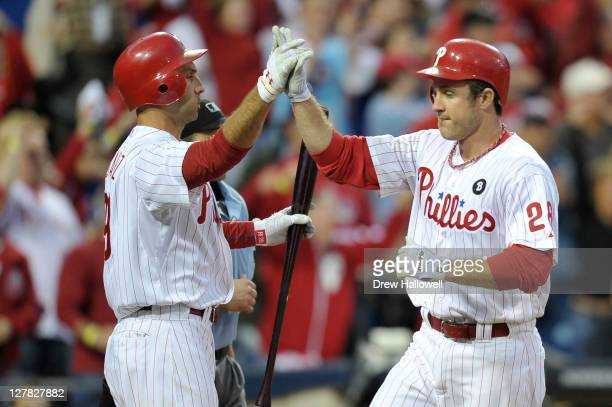 Chase Utley of the Philadelphia Phillies is congratulated by Raul Ibanez after scoring on a hit by Shane Victorino in the fourth inning of Game One...