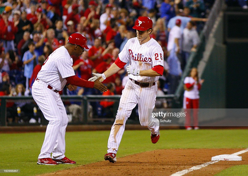 Chase Utley #26 of the Philadelphia Phillies is congratulated by third base coach Juan Samuel #12 after hitting a home run against the Atlanta Braves in the eighth inning during a MLB baseball game on September 21, 2012 at Citizens Bank Park in Philadelphia, Pennsylvania. The Phillies defeated the Braves 6-2.