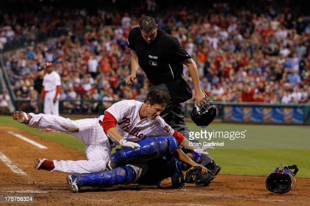 Chase Utley of the Philadelphia Phillies is tagged out as he collides with Dioner Navarro of the Chicago Cubs at the plate in the seventh inning of...