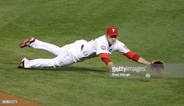Chase Utley of the Philadelphia Phillies makes a diving catch to stop a ground ball off the bat of Derek Jeter in the top of the first inning of Game...