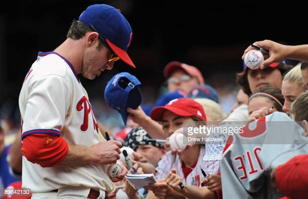 Chase Utley of the Philadelphia Phillies signs autographs before the game against the Colorado Rockies on August 6 2009 at Citizens Bank Park in...