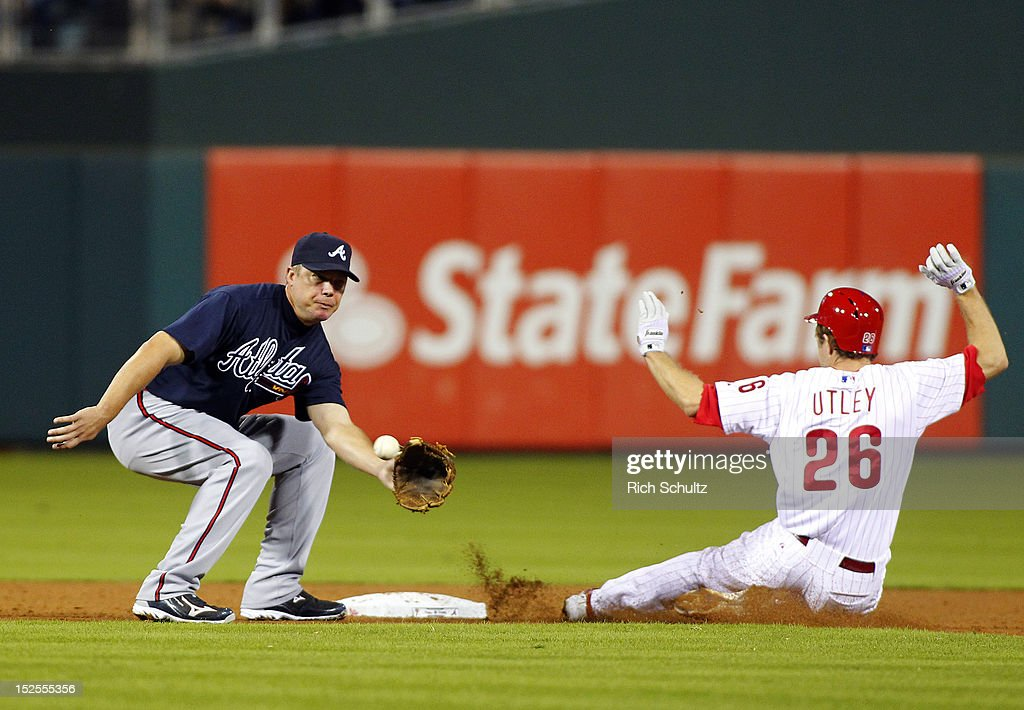 Chase Utley #26 of the Philadelphia Phillies steals second base before Chipper Jones #10 of the Atlanta Braves can apply the tag in the sixth inning during a MLB baseball game on September 21, 2012 at Citizens Bank Park in Philadelphia, Pennsylvania. The Phillies defeated the Braves 6-2.