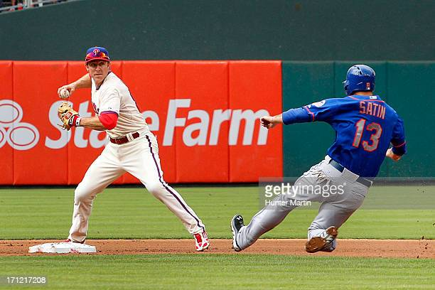 Chase Utley of the Philadelphia Phillies turns a double play as Josh Satin of the New York Mets slides into second during a game at Citizens Bank...