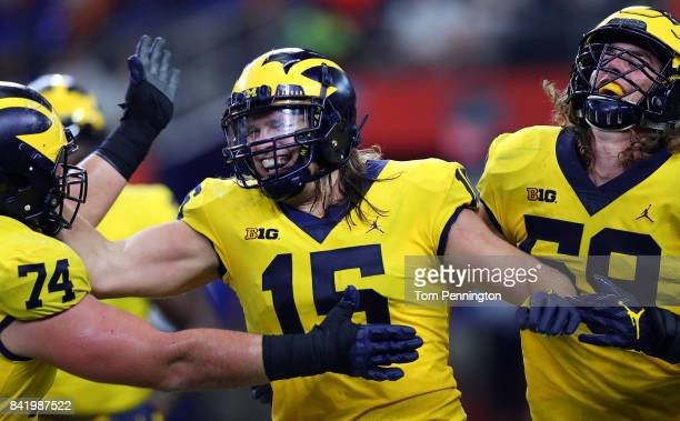 Chase Winovich of the Michigan Wolverines celebrates with Noah Furbush of the Michigan Wolverines and Ben Bredeson of the Michigan Wolverines after...