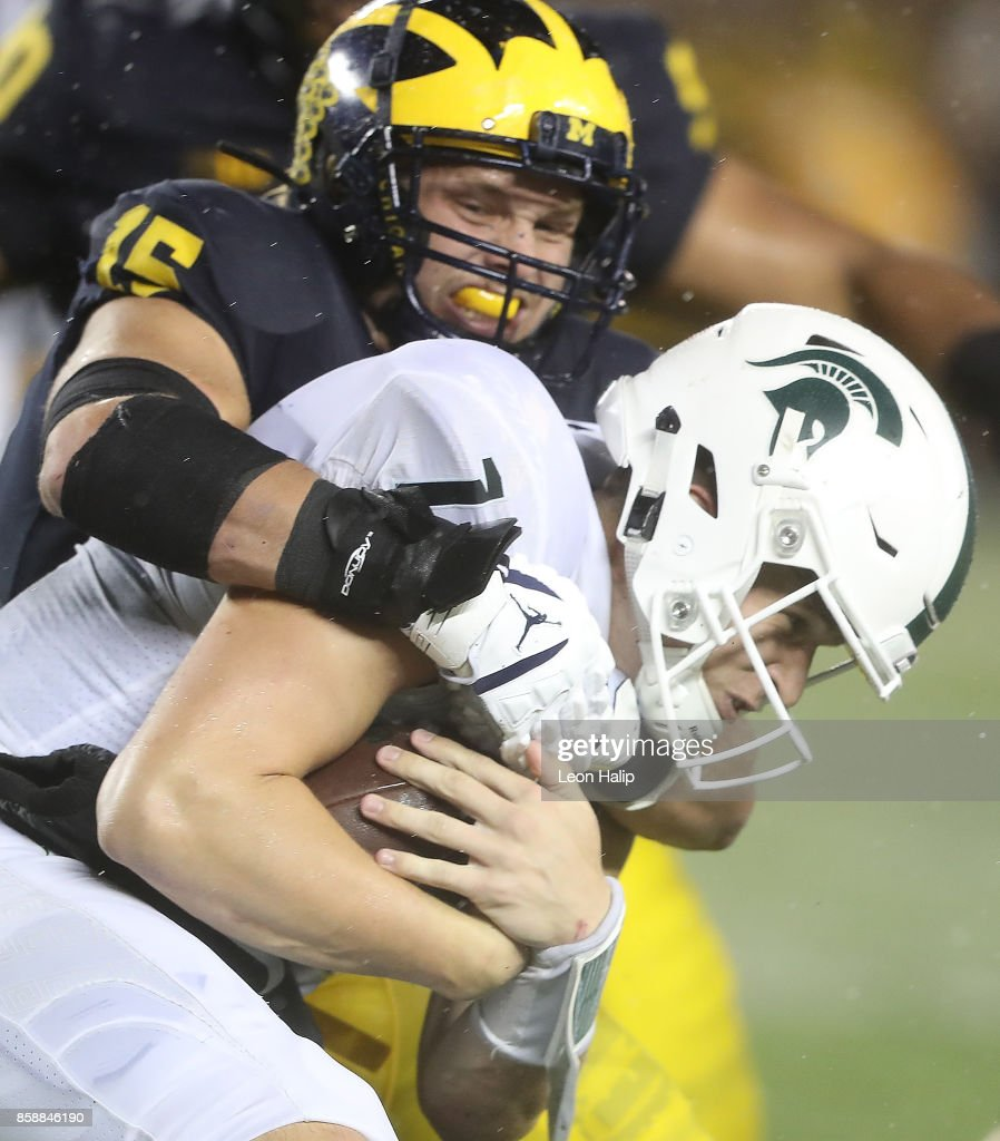 Chase Winovich #15 of the Michigan Wolverines makes the stop on Brian Lewerke #14 of the Michigan State Spartans during the fourth quarter of the game at Michigan Stadium on October 7, 2017 in Ann Arbor, Michigan. Michigan State defeated Michigan 14-10.