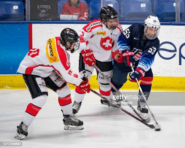 Chase Yoder of the US Nationals battles for the puck with Giancarlo Chanton and Joel Bieri of the Switzerland Nationals during day2 of game two of...