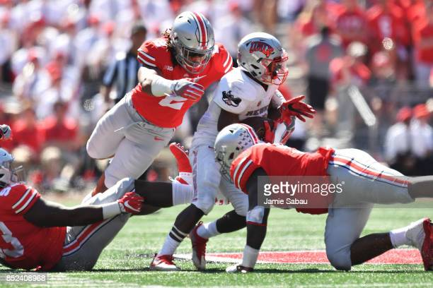 Chase Young of the Ohio State Buckeyes dives to make a tackle on Lexington Thomas of the UNLV Rebels in the second quarter at Ohio Stadium on...