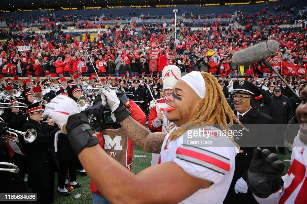 Chase Young of the Ohio State Buckeyes leads the Ohio State Marching Band in song after the win over the Michigan Wolverines at Michigan Stadium on...