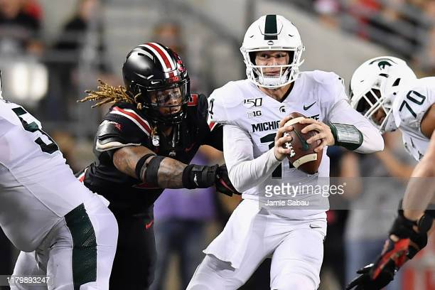 Chase Young of the Ohio State Buckeyes pressures quarterback Brian Lewerke of the Michigan State Spartans at Ohio Stadium on October 5 2019 in...
