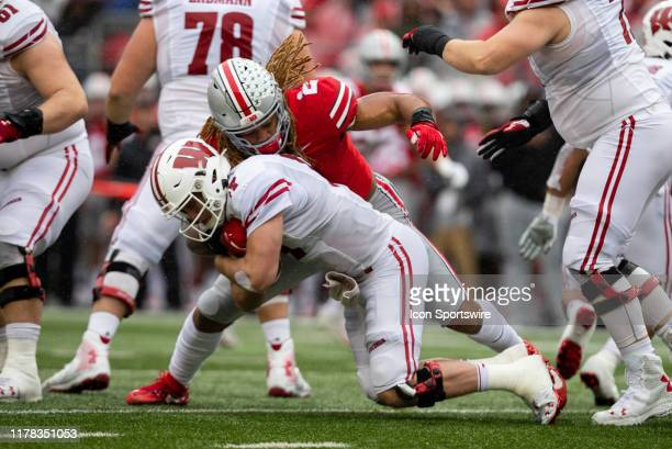 Chase Young of the Ohio State Buckeyes takes down Jack Coan of the Wisconsin Badgers during game action between the Ohio State Buckeyes and the...