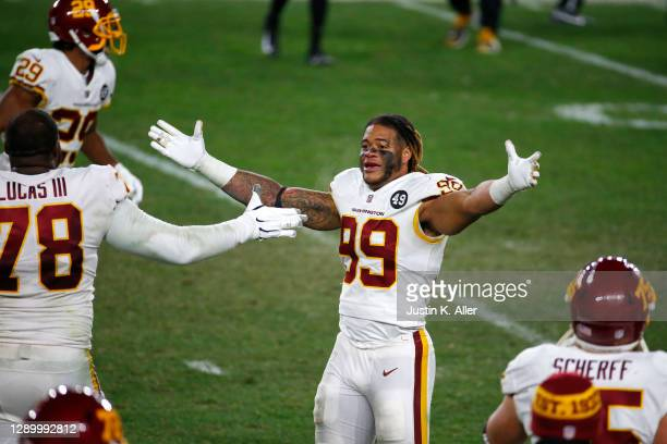 Chase Young of the Washington Football Team celebrates win teammate Cornelius Lucas III following their 23-17 win over the Pittsburgh Steelers at...