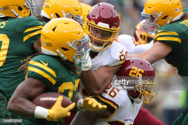 Chase Young of the Washington Football Team pursues Aaron Jones of the Green Bay Packers during a game at Lambeau Field on October 24, 2021 in Green...