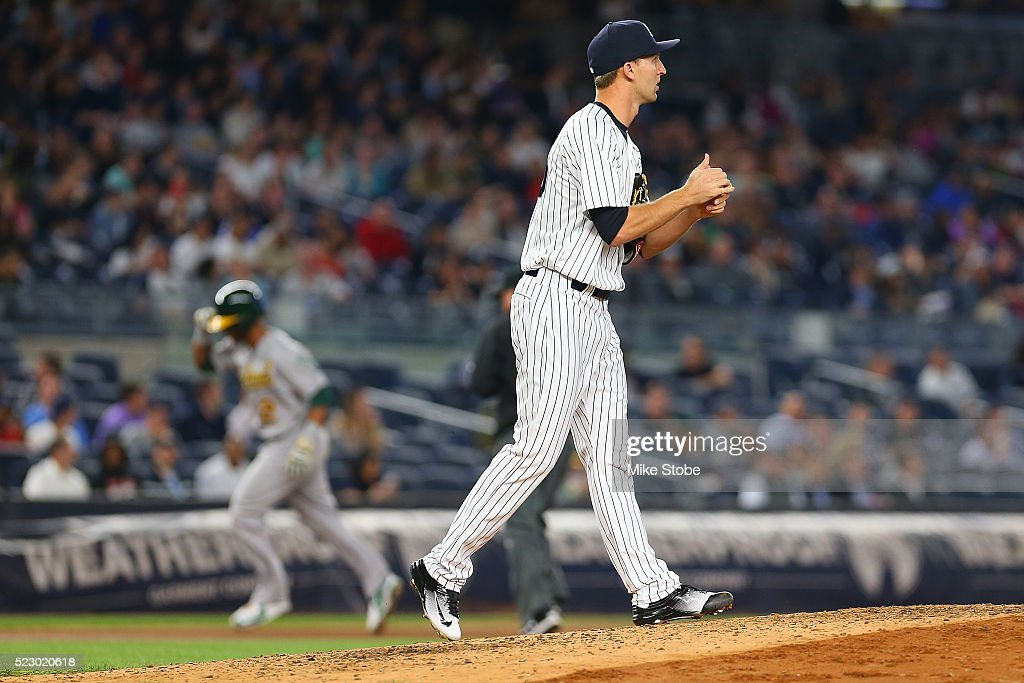 Chasen Shreve #45 of the New York Yankees looks on as Khris Davis #2 of the Oakland Athletics rouns third base after hitting a solo home run in the seventh inning at Yankee Stadium on April 21, 2016 in the Bronx borough of New York City.
