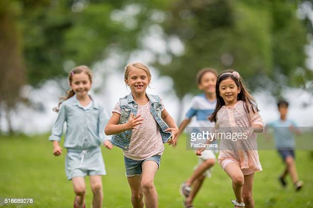 chasing each other at the park - kids playing tag stock photos and pictures