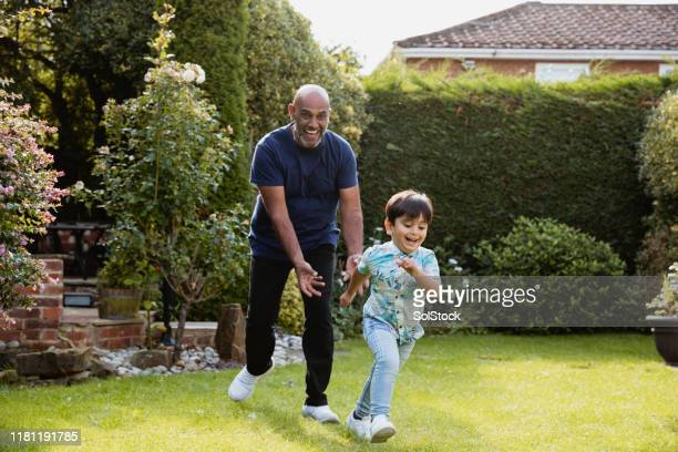 chasing grandson in garden - playing stock pictures, royalty-free photos & images