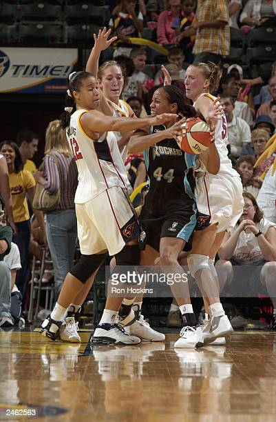Chasity Melvin of the Cleveland Rockers is defended by Natalie Williams Kelly Schumacher and Kristen Rasmussen of the Indiana Fever during the game...