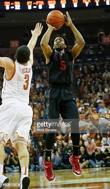 Chasson Randle of the Stanford Cardinal shoots over Javan Felix of the Texas Longhorns at the Frank Erwin Center on December 23 2014 in Austin Texas