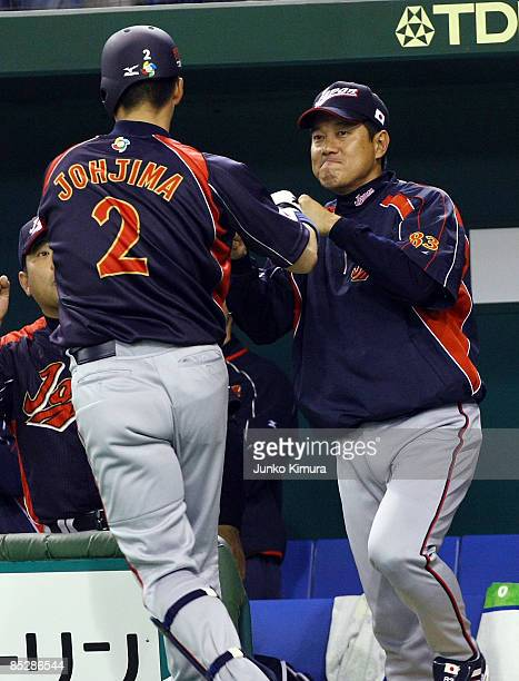 Chatcher Kenji Johjima of Japan celebrates after hitting a two run home run with Head Coach Tatsunori Hara of Japan in the top half of the sixth...