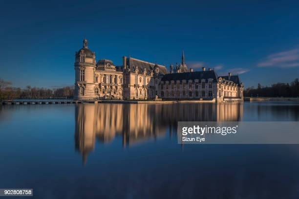 Chateau de Chantilly reflected in moats at the late afternoon, Oise department in France.