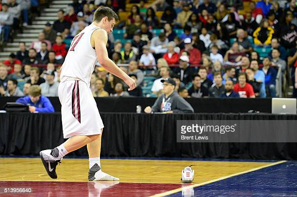 Chatfield guard Riley Welch walks back to his shoe after he lost it during the play before during the third quarter at the Denver Coliseum on March 5...