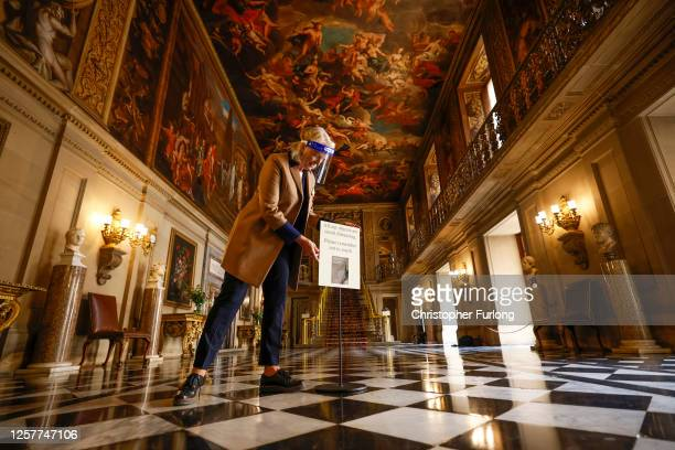 Chatsworth House guide Lizzie Ross poses for the media and adjusts a social distancing sign in the Painted Hall as the Derbyshire stately home...