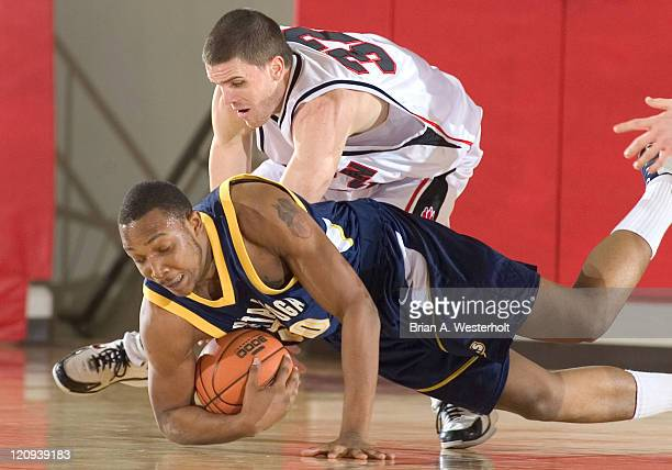 Chattanooga center Charles Anderson dives for a loose ball in front of Davidson guard Brendan Winters during first half action at Belk Arena in...