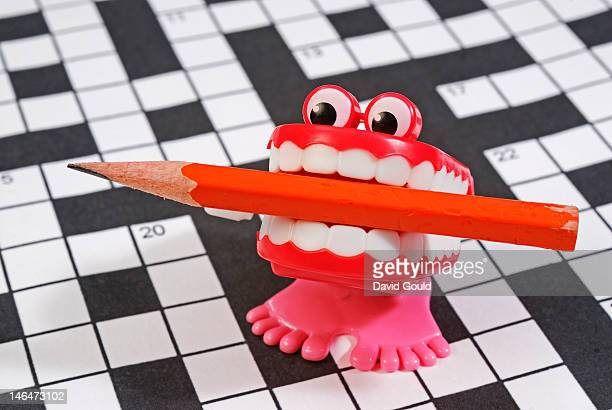 chatter teeth with pencil on a crossword puzzle - dentadura de brinquedo - fotografias e filmes do acervo